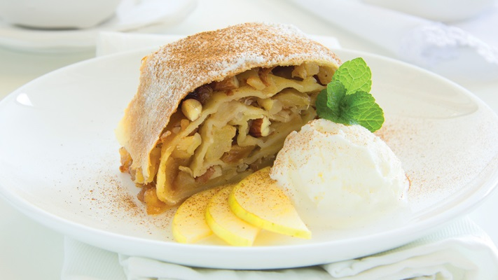 Apples layered in pastry with a sugar dusting served on a plate with icecream and garnish