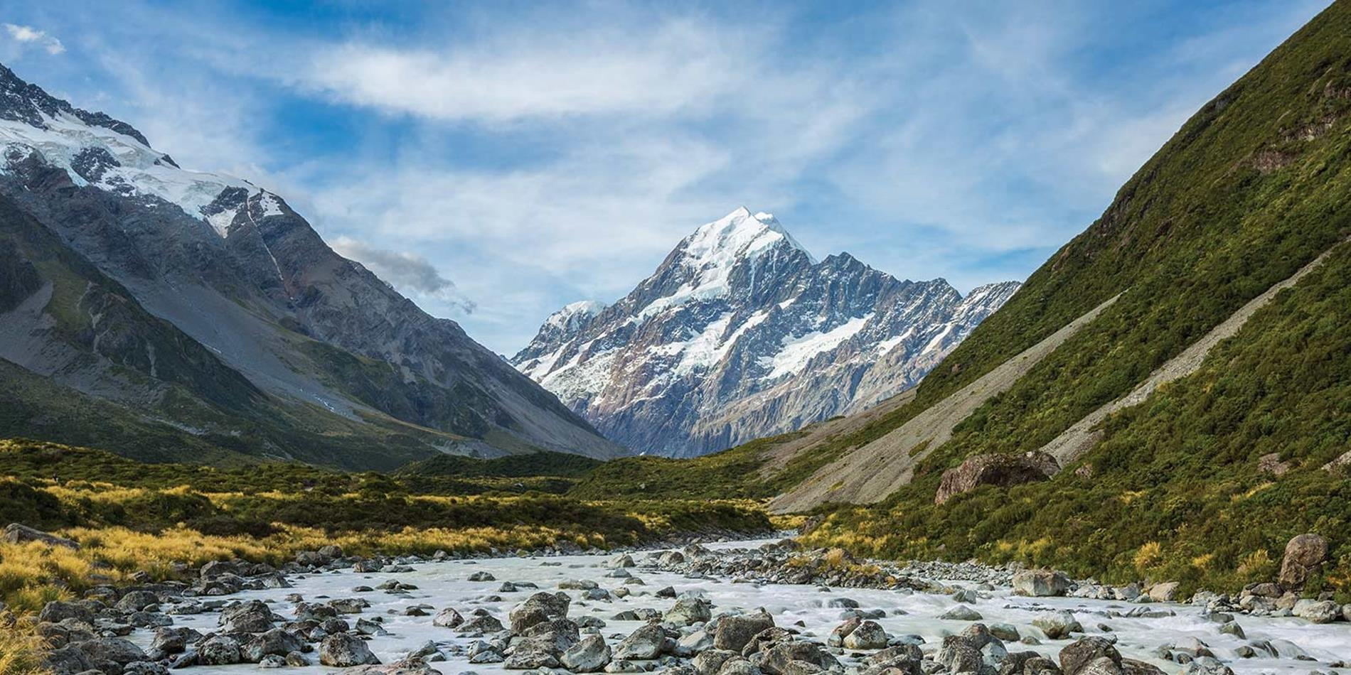 View from the valley looking up towards huge snow capped mountain, New Zealand