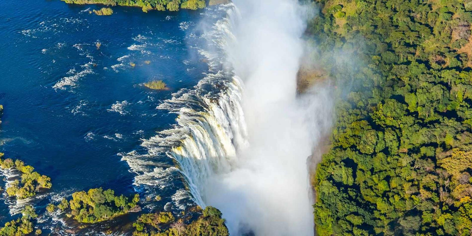 View of Victoria Falls from above rolling onto green below, Zambia