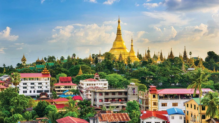 View of colourful town in front of golden pagoda, Myanmar