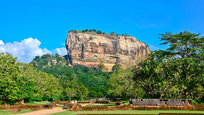 Large rock with blue sky in background and vegetation in foreground, Sri Lanka