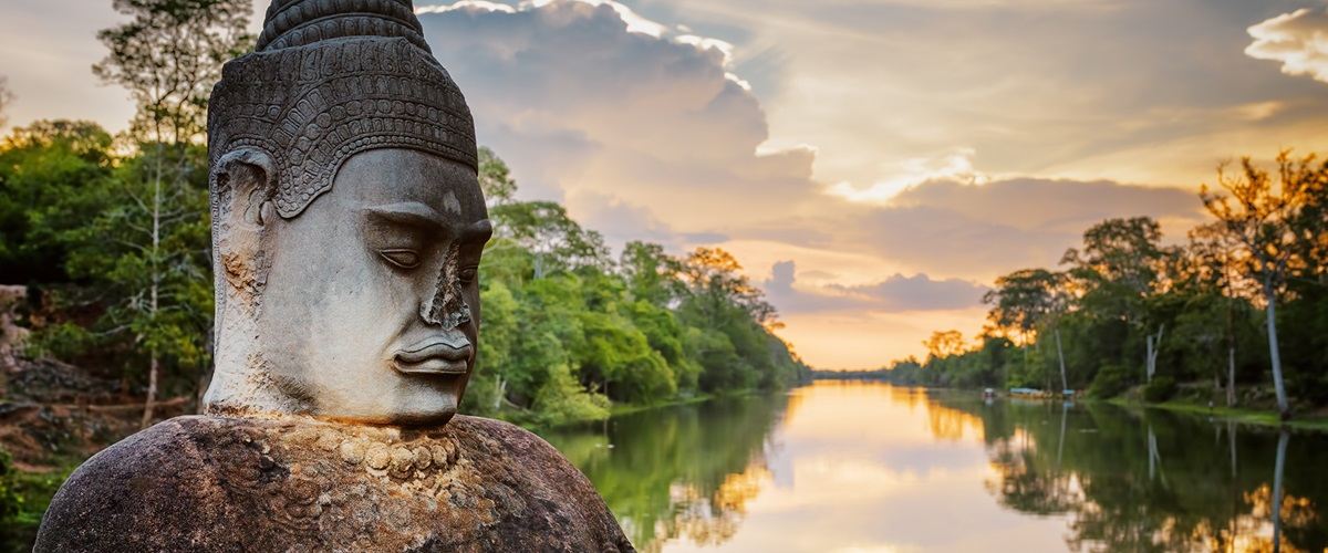 Statue in foreground with sunset over Angkor River, Cambodia