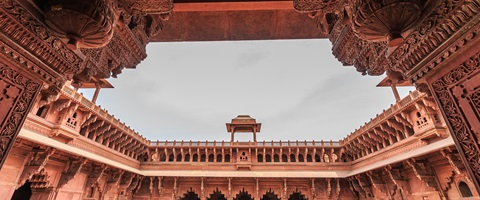 Red sandstone ornate structure of the building forecourt with open area in the middle