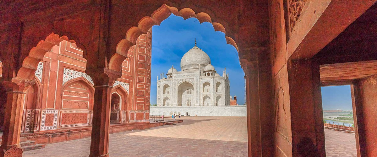 The Taj Mahal being viewed through an archway of a nearby building