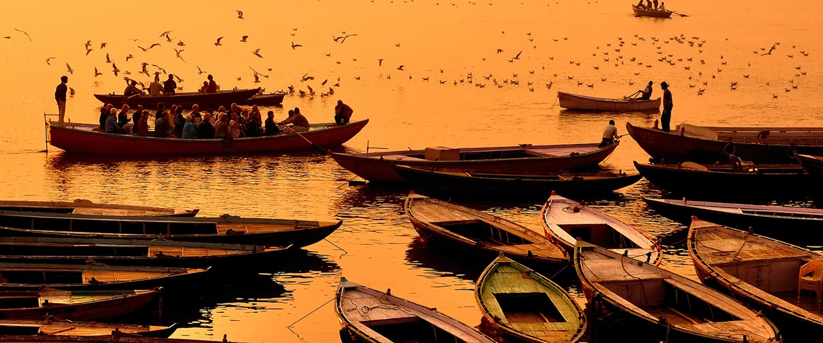 Fishermen on fishing boats in silhouette at sunset, Varinasi, India