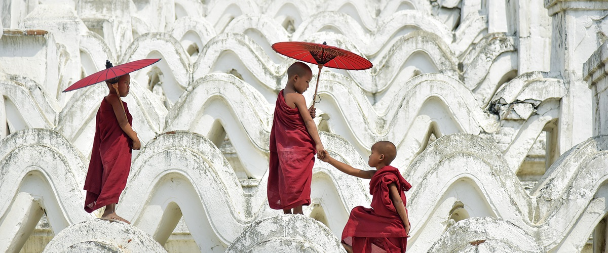 Three young monks climbing the white stone curves.
