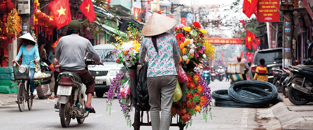 Vendor selling flowers through the streets of Hanoi