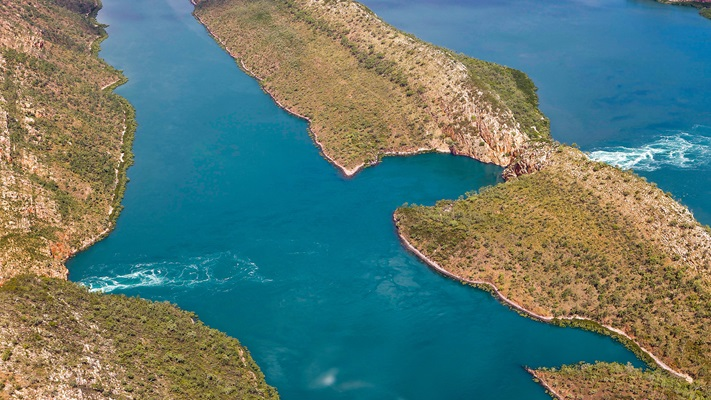 Aerial view over horizontal falls with red rocks and turqouise waters, WA
