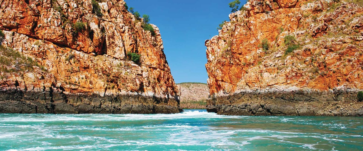 Two red cliff faces with water in between, Australia
