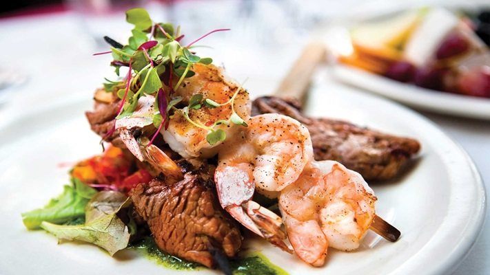 Prawns on a skewer resting on red meat and salad, Australia