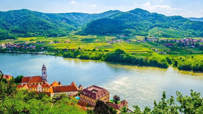 View across a lush green valley with a small village and river running alongside, Austria