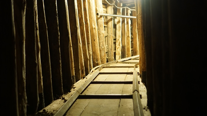 Dark narrow tunnell made of wooden boards heading towards the light
