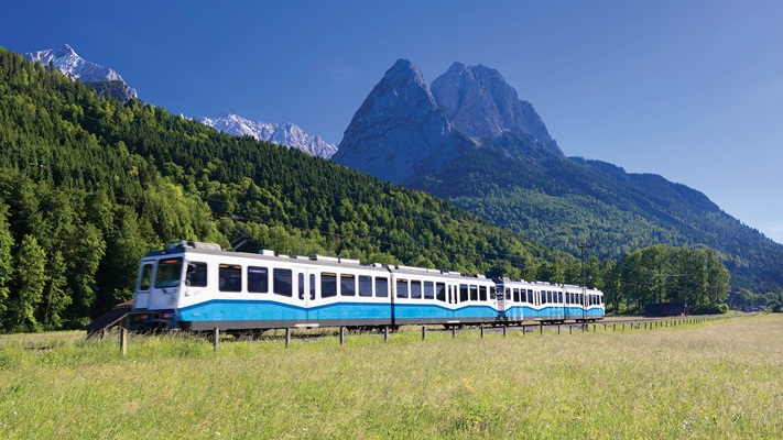 Small train travelling alongside alps, Germany