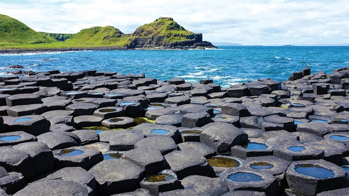 Large round rocks at the waters edge of a rugged sea, Ireland