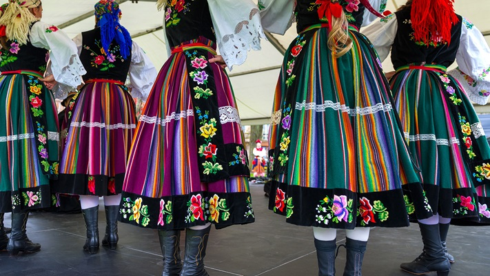 Group of ladies in colourful skirts doing traditional folk dancing, Poland