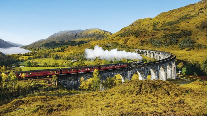 Red train travelling across a viaduct in the countryside, Scotland