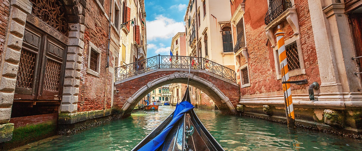 Gondola on canal heading towards a bridge, Venice, Italy