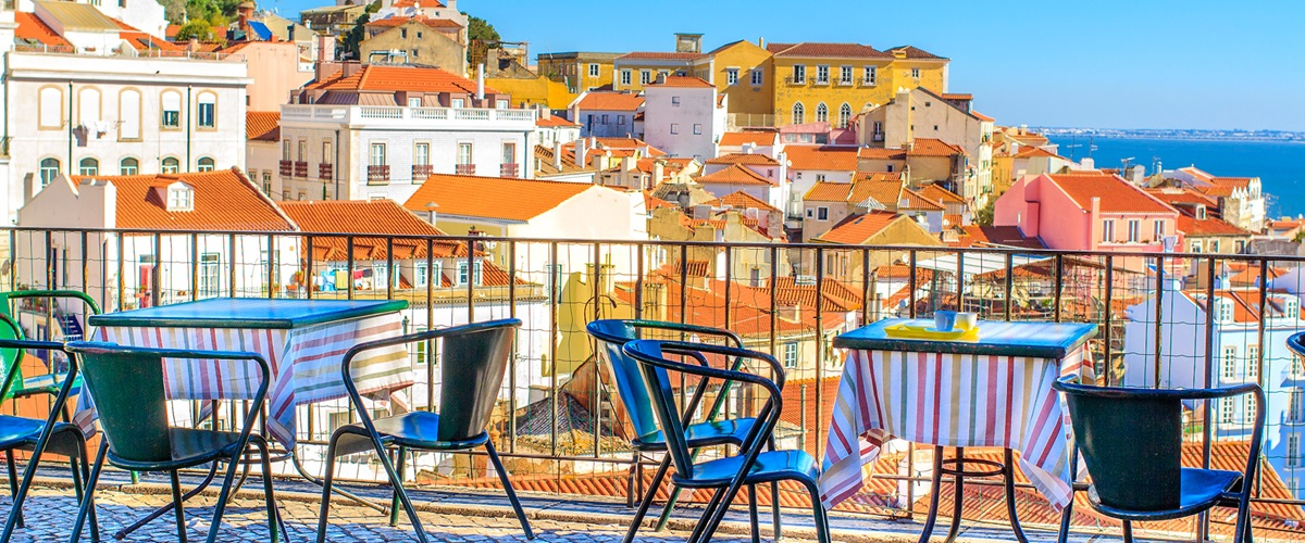 Seated meals area overlooking houses near water, Portugal, Lisbon