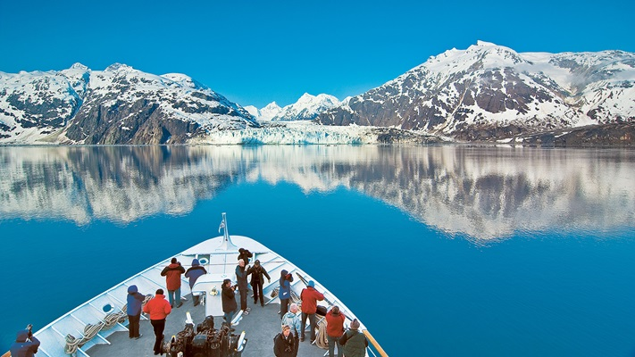 Snow capped mountains reflecting in the blue waters of the bay as we see passengers standing on the bow of the ship