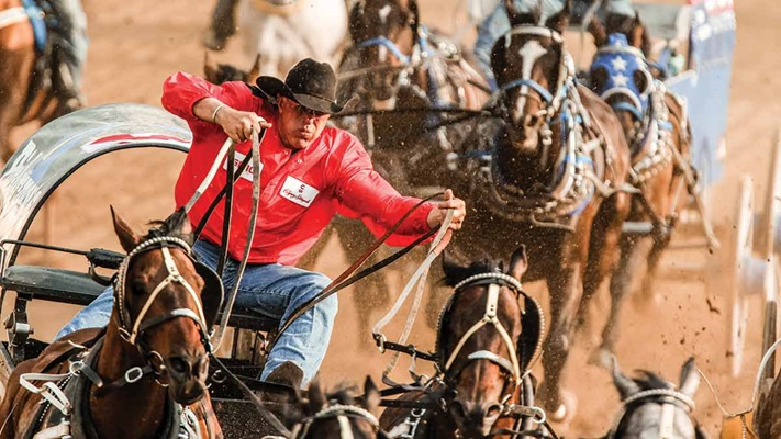 Man in red jacket and cowboy hat riding horses in a race, Canada