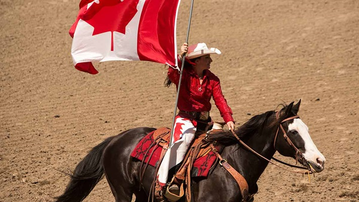 Horse rider in a red jacket holding Canadian flag, Canada