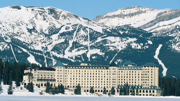 Hotel exterior with the moutains behind covered in snow at winter time