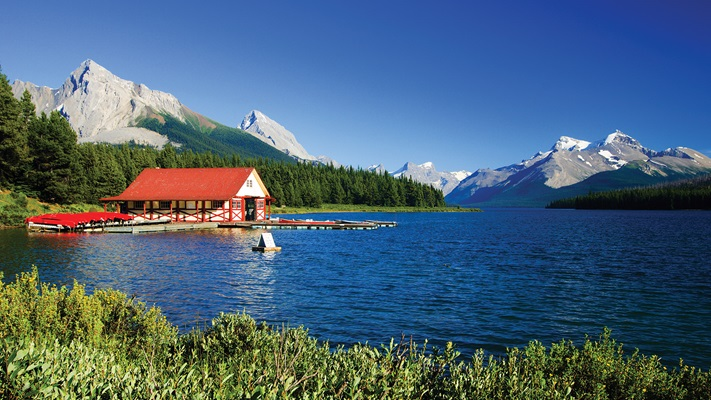 Green hedge borders the lake with boat shed and a back drop of the large rocky mountains in the background