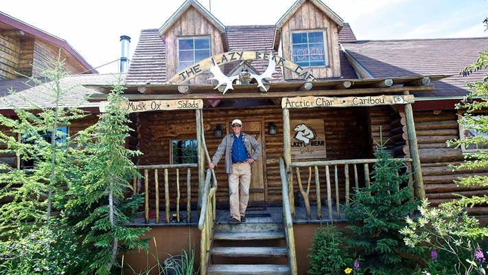 Man standing on steps of rustic cottage, Canada