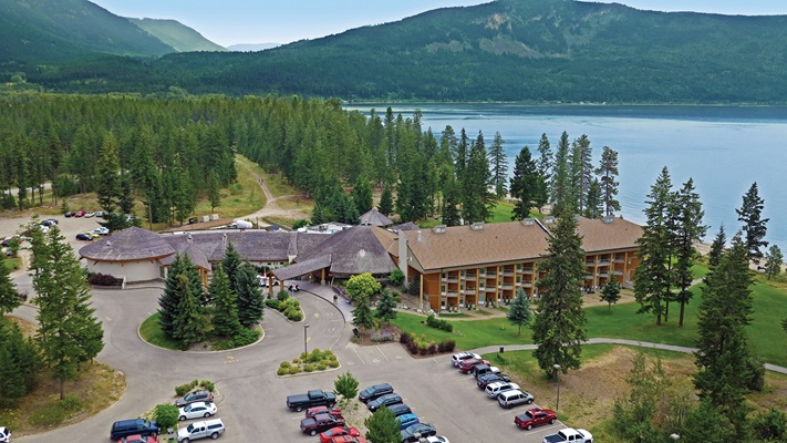 Aerial view of Quaaout lodge sitting amongst the tall trees beside the lake