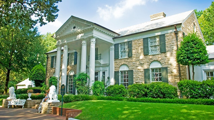 Drive way and manicured lawn leading to large two storey home made of blonde brick, green window shutters and tall pillars holding up portico