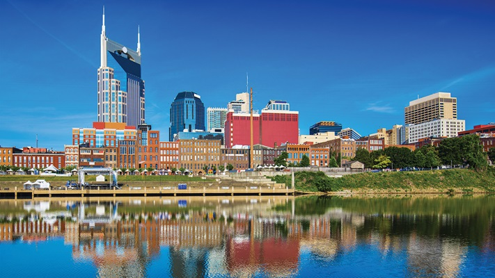 Nashville city skyline reflecting in the blue water on a clear sunny day