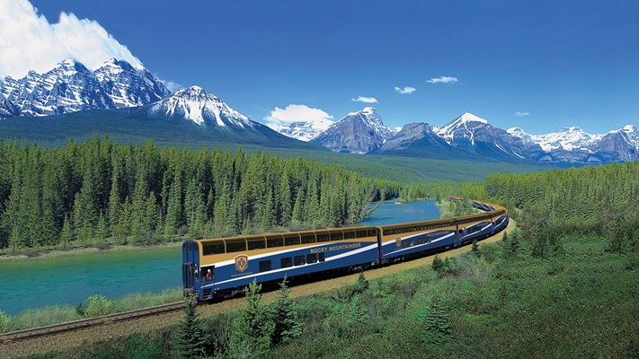 Rocky Mountaineer travelling through mountains by the side of river
