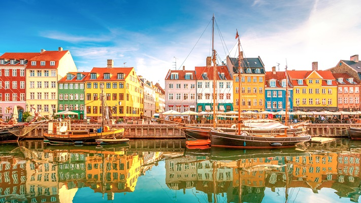 Row of coloured buildings along waterside with yachts moored, Denmark