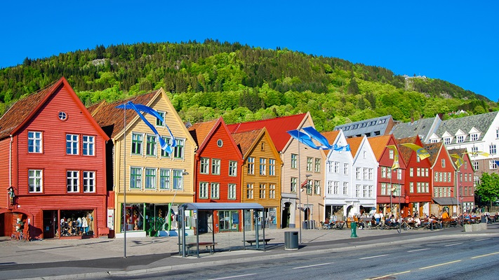 Bright coloured shops along a strip with mountain behind, Norway