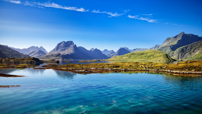 Pristine clear waters and huge barren mountains on a sunny day, Norway