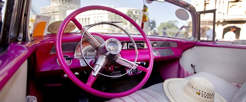 Pink colored sterring wheel white interior and sun hat on the seat