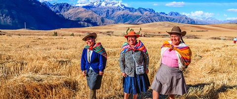 3 happy Peruian women walking through a field with mountains in background